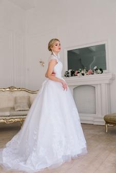 Linda noiva posando em vestido de noiva em um estúdio fotográfico branco, espelho e sofá.