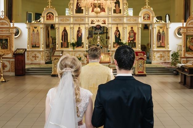 Linda noiva recém-casada com jaleco branco e noivo bonito valentynes beijando na frente da antiga igreja barroca