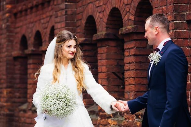 Linda noiva segurando um buquê de casamento, recém-casados de mãos dadas