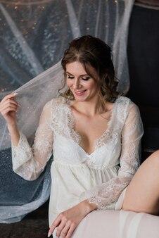 Linda noiva sexy em lingerie branca deitada na cama em seu quarto