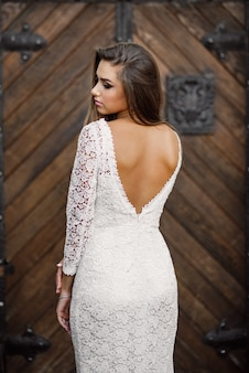 Linda noiva sexy encantadora em vestido de renda branca com costas nuas em portas de madeira velhas