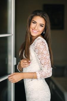 Linda noiva sorridente encantadora em vestido de renda branca com sorriso perfeito perto da porta da varanda