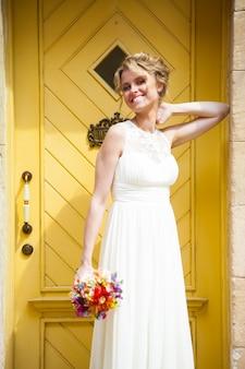 Linda noiva sorridente no dia do casamento com um grande buquê perto da igreja.