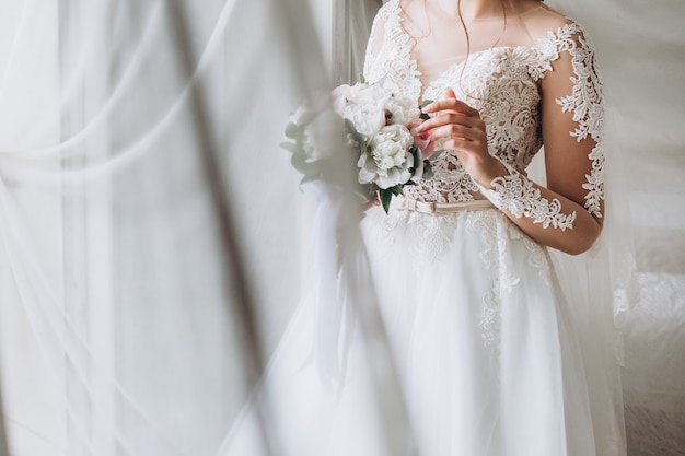 Linda noiva tem nas mãos um buquê de casamento com peônias.
