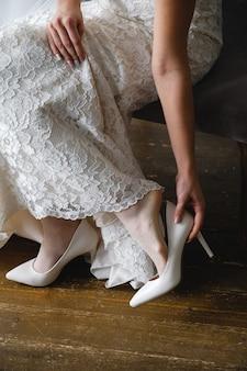 Linda noiva usa sapatos de casamento. fechar-se. dia do casamento ou de manhã.