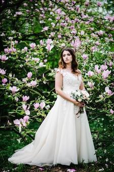 Linda noiva vestida de branco com um buquê posando e em pé na natureza de flores roxas, rosa de magnólia e verdes.