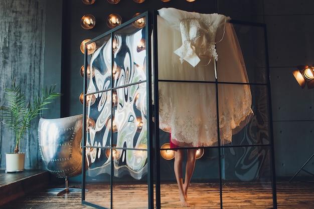 Linda, noiva vestido de luxo branco está se preparando para o casamento. preparativos da manhã. mulher colocando o vestido.