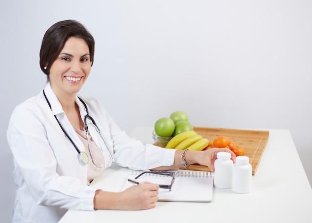 Linda nutricionista sorridente, olhando para a câmera e mostrando frutas saudáveis