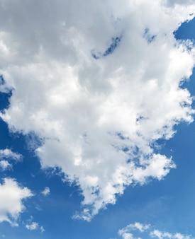 Linda nuvem branca e encaracolada no céu azul com tempo ensolarado, vertical e formato
