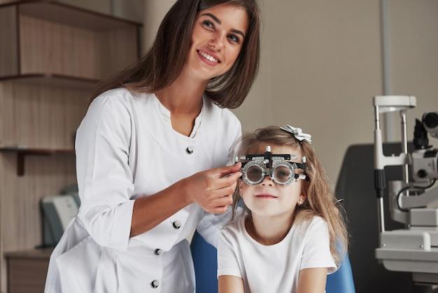 Linda oftalmologista sorrindo ao fazer seu trabalho no gabinete com a menina.