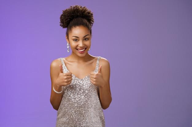 Linda ousada mulher afro-americana elegante vestido de noite prateado concorda ajudar mostrar polegares para cima aprovação como um gesto sorrindo amplamente recomendar um ótimo serviço, acho que a roupa combina com ela.