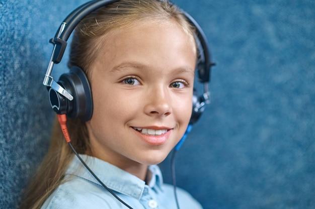 Linda paciente do sexo feminino sorrindo em fones de ouvido, olhando para o futuro