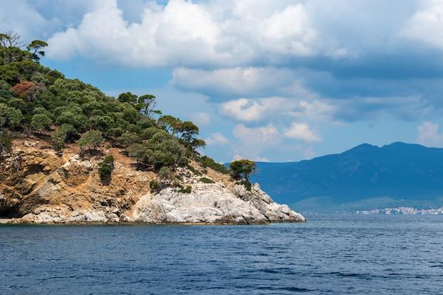 Linda paisagem com o mar, a rocha e as lindas nuvens no céu azul