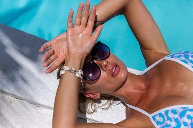 Linda pele bronzeada em forma de mulher caucasiana bronzeada brilhante em biquíni com óleo de coco à beira da piscina azul