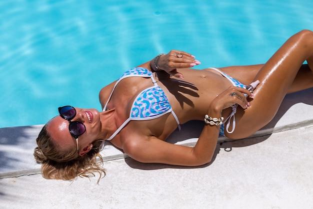 Linda pele bronzeada em forma de mulher caucasiana bronzeada brilhante em biquíni com óleo de coco à beira da piscina azul Foto gratuita