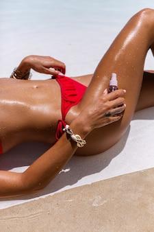 Linda pele bronzeada em forma de mulher caucasiana bronzeada brilhante em biquíni com óleo de coco