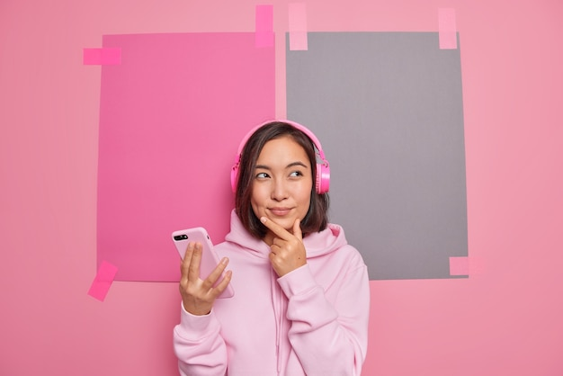 Linda pensativa jovem morena asiática segurando o queixo considera algo segura o celular pensa em como passar o fim de semana ouvindo música em fones de ouvido vestida casualmente poses contra o espaço em branco da cópia