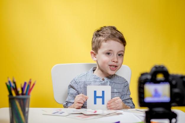 Linda pequena blogueira blogando sobre como aprender o alfabeto em fundo amarelo