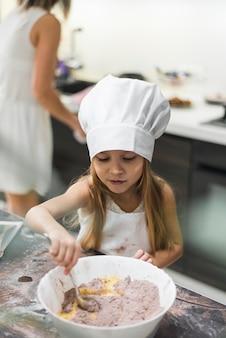 Linda pequena chef mistura pó de cacau e manteiga com colher