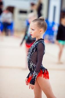 Linda pequena ginasta treinamento no tapete e pronto para competições