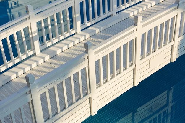 Linda ponte de madeira branca sobre a água ao sol