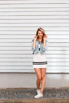 Linda positiva elegante jovem com roupas da moda de verão, posando na rua perto de um prédio vintage de madeira em um dia quente de verão