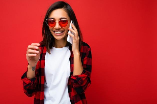 Linda positiva sorridente jovem morena usando uma elegante camiseta vermelha e óculos de sol vermelhos