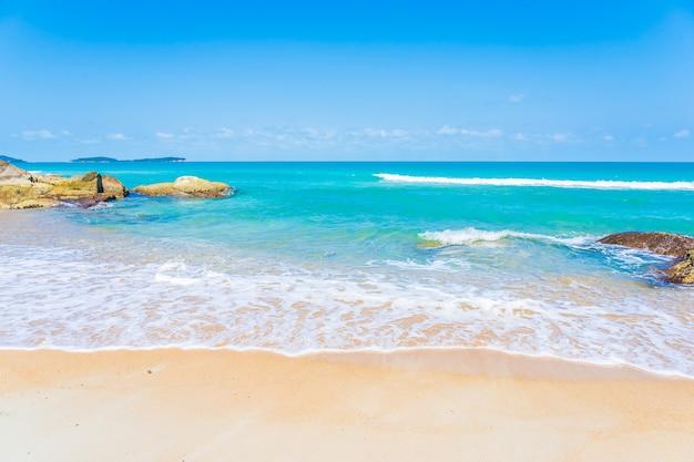 Linda praia tropical, mar, oceano, com nuvens brancas e fundo de céu azul para viagens de férias