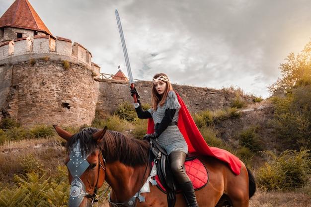 Linda princesa com capa vermelha e com uma espada andando a cavalo contra o pano de fundo de uma torre e