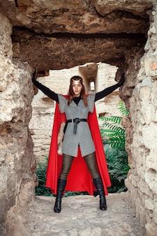 Linda princesa com capa vermelha e uma tiara dourada contra a parede de pedra da torre.