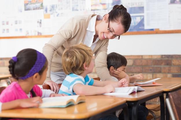 Linda professora ajudando o aluno em sala de aula