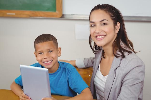 Linda professora e aluno com tablet na sua mesa