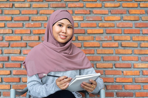Linda professora mulher muçulmana sentado na parede de tijolo