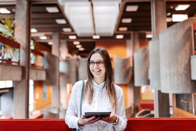 Linda professora sorridente com cabelos castanhos e óculos segurando o tablet