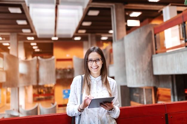 Linda professora sorridente com cabelos castanhos e óculos usando tablet