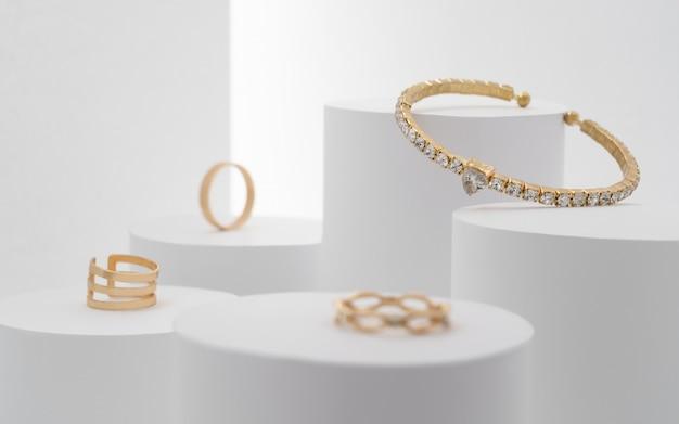 Linda pulseira preciosa com coleção de diamantes e anéis em plataformas brancas.