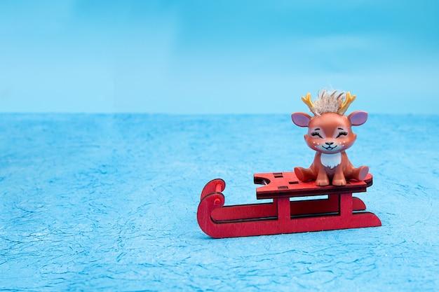 Linda rena de natal sentada em um trenó.