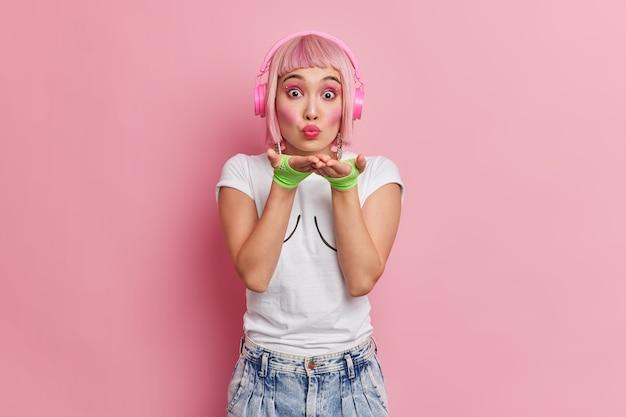 Linda romântica jovem asiática sopra beijo no ar na câmera tem cabelo bob rosa usa fones de ouvido estéreo nas orelhas ouve música da lista de reprodução vestida com camiseta de luvas de esporte e poses de jeans internas.