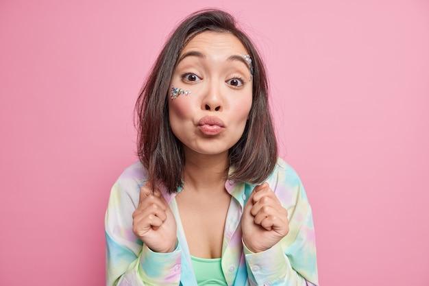 Linda romântica mulher asiática morena olha com ternura mantém os lábios dobrados em mwah quer te beijar usa poses de camisa colorida contra parede rosa se inclina para frente faz beijar o rosto.