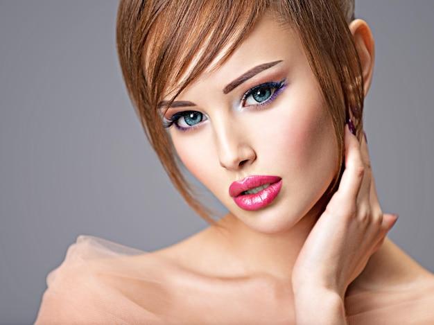 Linda ruiva com penteado de estilo. retrato de uma jovem sexy com grandes olhos azuis. poses de modelo de moda