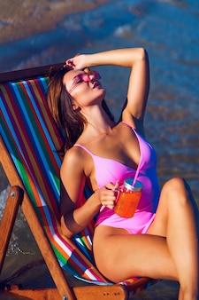 Linda ruiva em uma espreguiçadeira tomando sol perto do mar com um copo de suco na mão
