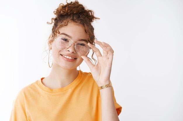 Linda ruiva europeia despreocupada e bagunçada hairbun tocando os óculos inclinando a cabeça sorrindo alegremente conversando com amigo sentindo-se alegre, expressando uma vibe lúdica positiva, autoconfiante