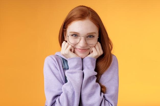 Linda ruiva fofa doce boba garota geek estudante universitária usando óculos mão magra sorrindo ternamente olhar carinho adoro ouvir confissões sensuais namorado, em pé fundo laranja