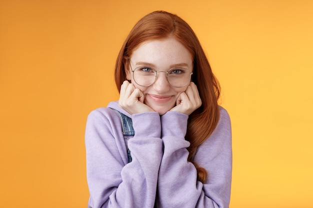 Linda ruiva fofa doce boba menina geek estudante universitário usando óculos mão magra sorrindo ternamente olhar carinho adoro ouvir confissões sensuais namorado, em pé fundo laranja.