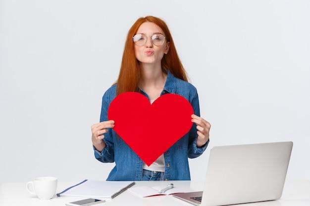 Linda ruiva linda romântica, dobrando os lábios em mwah, mande beijo do ar e segurando o cartão de dia dos namorados vermelho grande, mostrando seu amor e paixão, parabenizar a namorada com aniversário, ficar perto do laptop