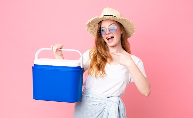 Linda ruiva parecendo animada e surpresa, apontando para o lado e segurando uma geladeira portátil de piquenique