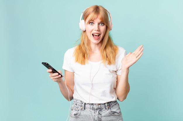 Linda ruiva se sentindo feliz e surpresa com algo inacreditável e ouvindo música com fones de ouvido