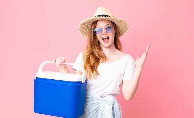 Linda ruiva se sentindo feliz, surpresa ao perceber uma solução ou ideia e segurando uma geladeira portátil de piquenique
