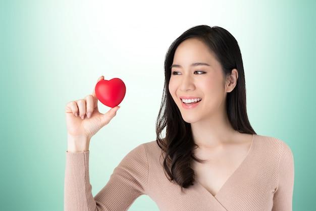 Linda saudável jovem mulher asiática com bola de coração vermelho