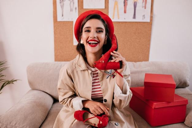 Linda senhora adorável na boina elegante brilhante e bege trincheira de outono se divertindo em seu apartamento e segura sapatos vermelhos.